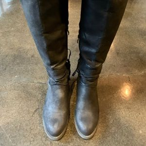 Women's knee high black boots with laces.